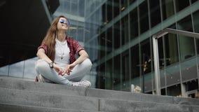 Portret piękna kobieta siedzi na kamienistych schodkach na tle nowożytny szklisty budynek w przypadkowych ubraniach zbiory wideo