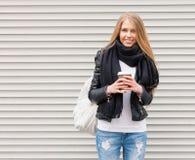 Portret piękna młoda blondynki dziewczyna z długie włosy pozować na ulicie z kawą i plecakiem Spojrzenie przy kamerą Outdoo Fotografia Royalty Free