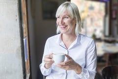 Portret piękna młoda blondynki kobieta cieszy się herbacianą filiżankę Zdjęcie Stock