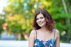 Portret piękna młoda brunetki dziewczyna z falistym włosy w krótkiej sukni w parku obraz stock
