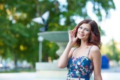 Portret piękna młoda brunetki dziewczyna z falistym włosy w krótkiej sukni w parku obrazy stock