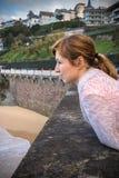 Portret piękna młoda czerwona z włosami kobieta opiera na ścianie, obserwujący fala i surfingowów na brzeg atlantycki wybrzeże Zdjęcie Stock