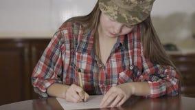Portret piękna młoda dziewczyna siedzi w domu na stole i pisać liście w żołnierz nakrętce zdjęcie wideo
