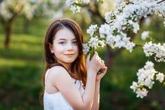 Portret piękna młoda dziewczyna z niebieskimi oczami w biel sukni w ogródzie z jabłoniami blosoming przy zmierzchem obraz royalty free