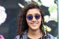 Portret piękna młoda etniczna dziewczyna jest ubranym chłodno hełmofony, okulary przeciwsłonecznych i cienie na miasto ulicie lub Obraz Royalty Free