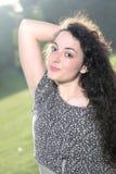 Portret piękna młoda kędzierzawa dziewczyna przeciw światłu Zdjęcie Stock