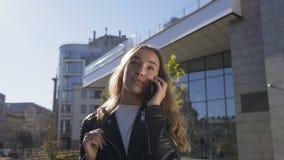 Portret pi?kna m?oda kobieta chodzi na miasto ulicie podczas gdy opowiadaj?cy z jej przyjacielem na smartphone dosy? zbiory