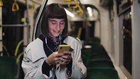 Portret piękna młoda kobieta jedzie publicznie transport w hełmofonach, słucha muzycznego i wyszukiwać na kolorze żółtym zbiory