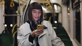 Portret piękna młoda kobieta jedzie publicznie transport w hełmofonach, słucha muzycznego i wyszukiwać na kolorze żółtym zbiory wideo