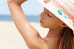 Portret piękna młoda kobieta w bikini z słomianym słońce kapeluszem na plaży z piaskiem, morzem i niebem w tle, Zdjęcie Stock