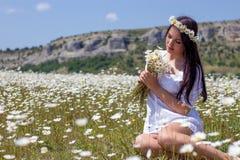 Portret piękna młoda kobieta w chamomile polu Szczęśliwej dziewczyny zbierackie stokrotki Dziewczyna odpoczywa w polu chamomile S Fotografia Stock