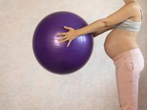 Portret piękna młoda kobieta w ciąży ćwiczy z czerwonym fitball w gym Opracowywać i sprawność fizyczna, zdjęcia stock