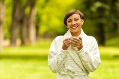 Portret piękna młoda kobieta z filiżanki pozycją zdjęcie stock