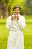 Portret piękna młoda kobieta z filiżanki pozycją w dziąsłach Obraz Stock