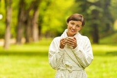 Portret piękna młoda kobieta z filiżanki pozycją w dziąsłach zdjęcie royalty free