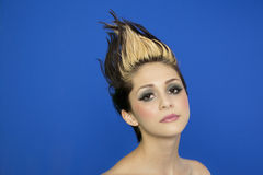 Portret piękna młoda kobieta z gwożdżącym włosy pozuje nad błękitnym tłem Zdjęcia Stock