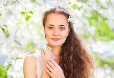 Portret piękna młoda kobieta z kwiatami nad wiosna ogródem zdjęcia royalty free