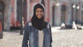 Portret piękna młoda Muzułmańska kobieta jest ubranym hijab chustkę na głowę ono uśmiecha się w kamery pozycję na starym mieście zdjęcie wideo