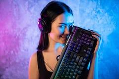 Portret Piękna Młoda Pro Gamer dziewczyny pozycja z i spojrzenia w kamerę hazard słuchawki i klawiaturą obrazy royalty free