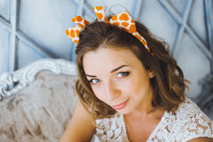 Portret piękna młoda słodka dziewczyna z powabnym uśmiechem i rogami na głowie żyrafa pozuje i ono uśmiecha się Obrazy Royalty Free