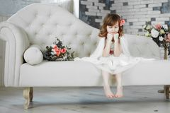 Portret piękna mała dziewczynka w biel sukni na białej kanapie zdjęcia stock