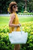 Portret Piękna modna caucasian brunetki kobieta z okularami przeciwsłonecznymi i luksusowym snakeskin pytonu torebki pozować Zdjęcia Stock