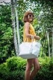 Portret Piękna modna caucasian brunetki kobieta z okularami przeciwsłonecznymi i luksusowym snakeskin pytonu torebki pozować Zdjęcia Royalty Free