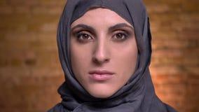 Portret piękna muzułmańska kobieta ogląda poważnie w kamerę w hijab z jaskrawym makijażem dalej bricken ścianę zbiory wideo