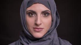 Portret piękna muzułmańska kobieta ogląda pozytywnie w kamerę na czarnym tle w hijab z jaskrawym makijażem zbiory