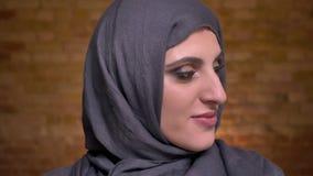 Portret piękna muzułmańska kobieta shyly obraca jej głowę i ono uśmiecha się w kamerę dalej w hijab z jaskrawym makijażem zdjęcie wideo