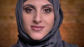 Portret piękna muzułmańska kobieta w hijab z jaskrawym makijażem obraca jej głowę i ono uśmiecha się w kamerę dalej bricken ścian zbiory