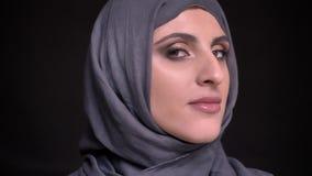Portret piękna muzułmańska kobieta w hijab z jaskrawym makijażem obraca jej głowę i ono uśmiecha się w kamerę na czerni zbiory wideo