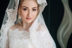 Portret piękna panna młoda z brązem ono przygląda się, blondynka kędziory ubierający w białej kręconej sukni i przesłona obrazy royalty free