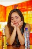 Portret piękna pijąca kobieta pozuje jej ręki w jej podbródku z butelką piwa, wody i samochodu klucze nad a, Obrazy Stock