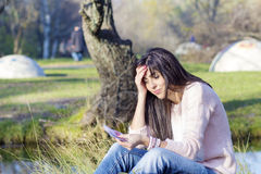 Portret piękna roześmiana kobieta liczy jej pieniądze w parku Zdjęcia Stock