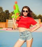 Portret piękna seksowna dziewczyna pozuje w drelichów skrótach, biała koszulka i okulary przeciwsłoneczni w, jeździć na łyżwach p zdjęcie royalty free