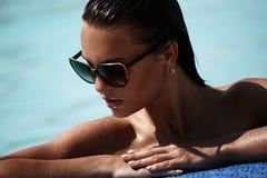 Portret piękna seksowna dziewczyna z okularami przeciwsłonecznymi w pływackim basenie obrazy stock