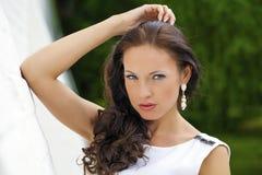 Portret piękna smutna dziewczyna w biel sukni opiera na wal fotografia stock