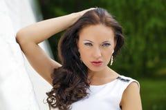 Portret piękna smutna dziewczyna w biel sukni opiera na wal zdjęcia stock
