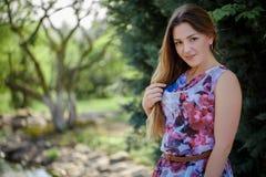 Portret piękna szczęśliwa kobieta cieszy się odór w kwiatonośnym wiosny kwitnienia ogródzie Jaskrawa i modna uśmiechnięta dziewcz zdjęcie royalty free