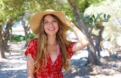 Portret piękna uśmiechnięta dziewczyna jest ubranym kapelusz i czerwieni smokingową patrzeje kamerę outdoors obrazy stock