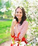 Portret piękna uśmiechnięta młoda kobieta w kwiatonośnym wiosna ogródzie Zdjęcie Royalty Free