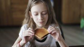 Portret piękna uczennica je białego chleba grzankę zdjęcie wideo