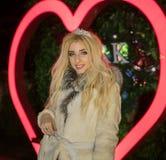 Portret Piękna wspaniała blondynki dziewczyna w Futerkowego żakieta posingin przodzie Neonowy serce znak zdjęcie royalty free