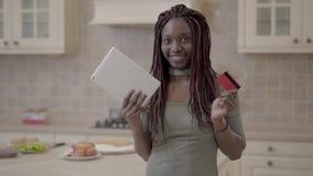 Portret pięknego amerykanin afrykańskiego pochodzenia uśmiechnięta kobieta bierze pastylkę i kartę kredytową po pomyślnej transak zdjęcie wideo
