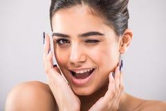 Portret pięknej kobiety figlarnie twarz z uśmiechem i mrugnięciem na popielatym tle Zdjęcia Royalty Free