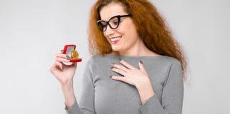 Portret pięknej rudzielec szczęśliwa uśmiechnięta młoda kobieta patrzeje na bitcoin jako cryptocurrency w szarość ubraniach w szk Zdjęcia Royalty Free