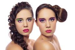 Portret piękni bliźniaków potomstwa fasonuje kobiety z fryzurą i czerwieni menchie zielenieją makeup pojedynczy białe tło fotografia stock