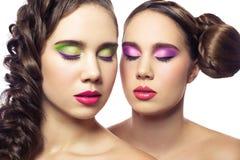 Portret piękni bliźniaków potomstwa fasonuje kobiety z fryzurą i czerwieni menchie zielenieją makeup pojedynczy białe tło Zdjęcia Royalty Free