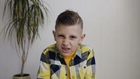 Portret piękni gniewający 7, 8 rok chłopiec która siedzi na podłoga nad biel ściany tłem - Chłopiec robi gniewnej twarzy i zdjęcie wideo
